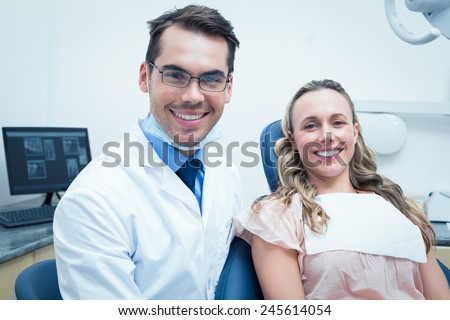 Dentist examining young womans teeth in the dentists chair - stock photo