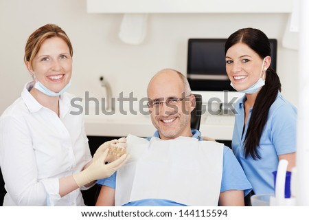 Dentist explaining teeth model to male patient at clinic while looking at camera