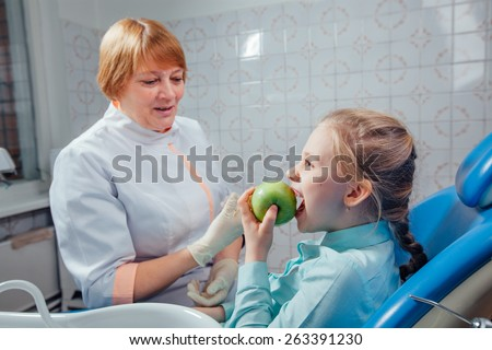 Dentist gives the child a green apple - stock photo