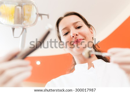 Dentist holding dental instruments and preparing for consultation