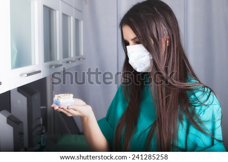 Dentist holding prosthetic teeth.Smiling female dentist holding artificial teeth model.Dental technician holding cast teeth model in dental laboratory. - stock photo
