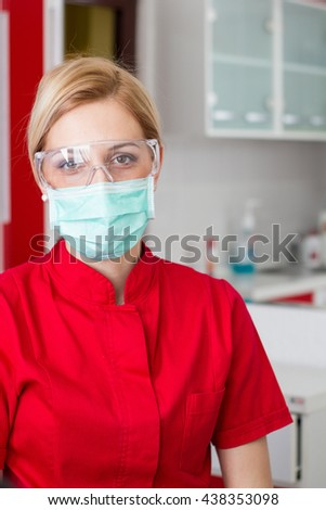 Dentist in a red uniform - professional doctor at work with mask and glasses - stock photo