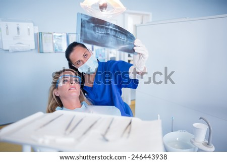 Dentist in mask explaining x-ray to patient at the dental clinic - stock photo