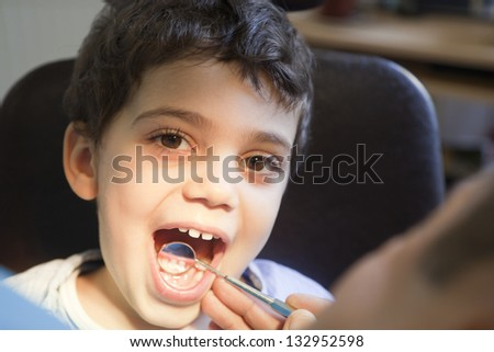 Dentist is checking and treating little boy's teeth. - stock photo