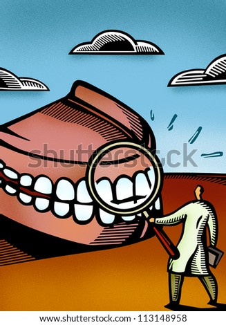 Dentist looking at giant dentures through a magnifier - stock photo