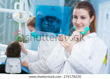 Dentist looking at roentgen of human jaw. Consulting. Patient blurred on chair in background. - stock photo