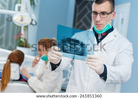 Dentist looking at roentgen, other female dentist examining a patient in background. Bright dentist office. Empty space for text. - stock photo