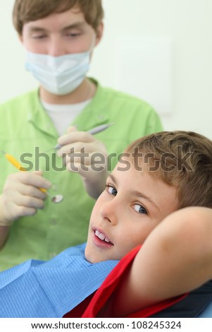 Dentist prepares to treat teeth of boy in dental clinic. Boy lies in chair. Focus on patient. - stock photo