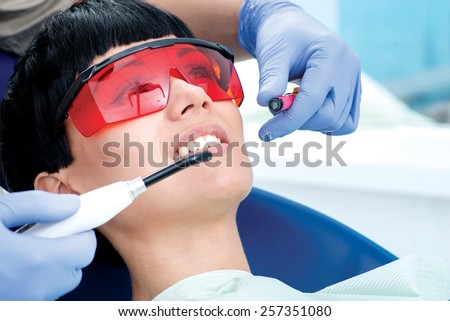 Dentist puts polymer seal. Dentist makes the process of treatment of a beautiful young girl. Woman in protective glasses - stock photo