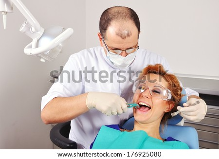 dentist removes the tooth beautiful girl - stock photo