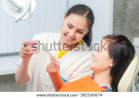 Dentist show dentures to a patient - stock photo