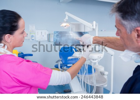 Dentist showing x-ray to his assistant at the dental clinic - stock photo