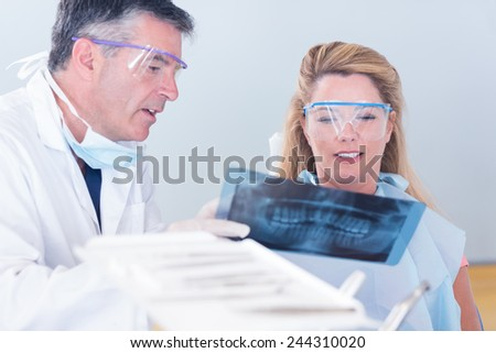 Dentist showing x-ray to his patient at the dental clinic - stock photo