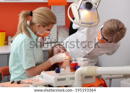 Dentist student examine  tooth of a young patient with professor looking - stock photo