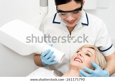 Dentist take jaw x-ray of female patient - stock photo