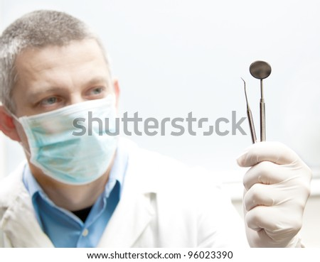 dentist tools in a doctor hand - stock photo
