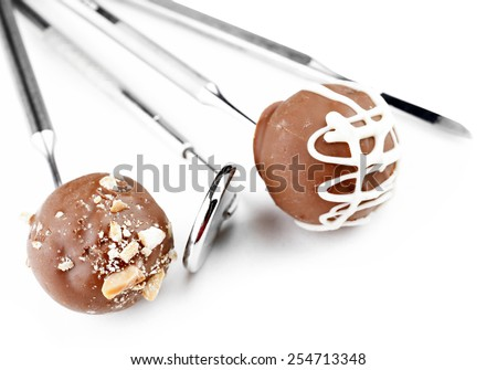 Dentist tools with sweets isolated on white - stock photo