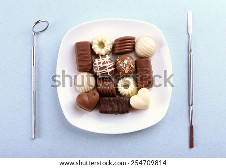 Dentist tools with sweets on plate on light background - stock photo