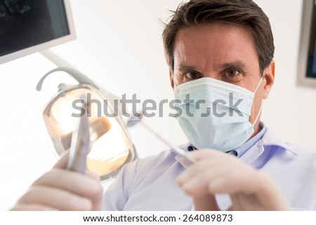 Dentist treating a tooth, point of view of the patient