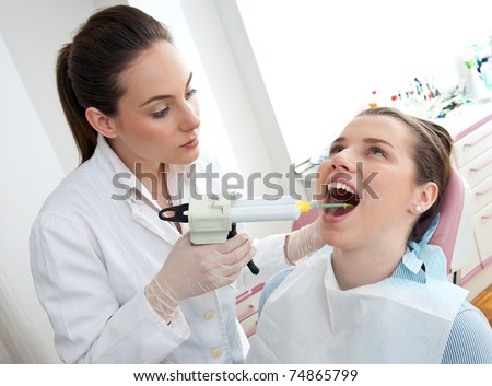 dentist using dental filling gun on woman - stock photo