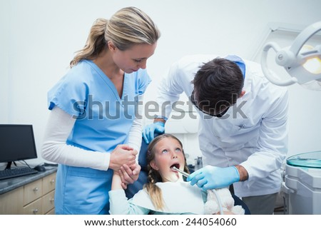 Dentist with assistant examining girls teeth in the dentists chair - stock photo