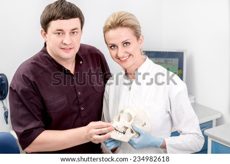 Dentist with assistant talking and holding artificial jaw in the dental office