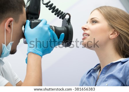 Dentist with camera making shots of patients smile after treatment. Special camera with flash ring shadowless.