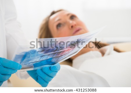 Dentist With Teeth X-ray In Front Of Happy Woman In Clinic - stock photo