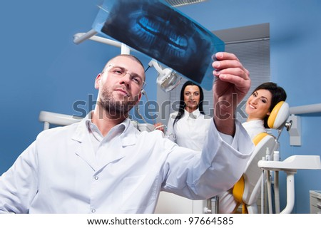 Dentist with x-ray and smiling patient with assistant in the background - stock photo