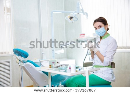 Dentist woman with medical instruments in the dental office