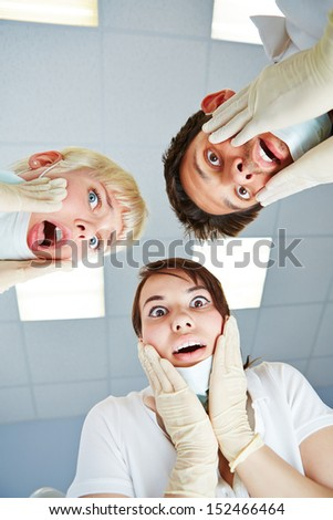 Dentists during dental treatment looking shocked at patient POV - stock photo