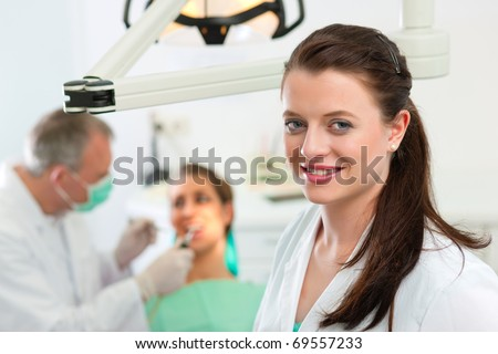 Dentists in her surgery looking at the viewer, in the background her colleague is giving a female patient a treatment - stock photo