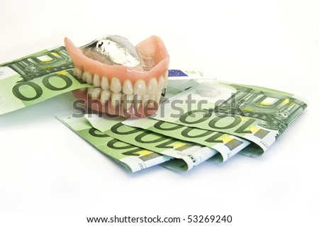 Dentures and money on white background