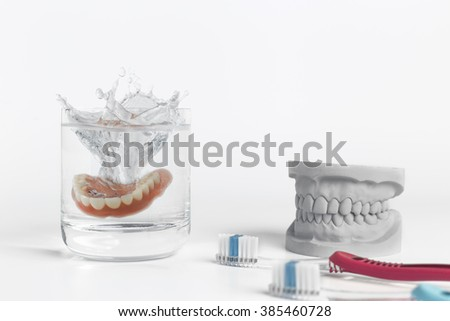 Dentures hygiene concept displaying mold falling into glass of water and pair of toothbrushes on white background - stock photo