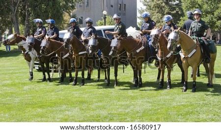DENVER - AUGUST 26: A line of police officers wait on horseback during the Democratic National Convention August 26, 2008 in Denver. - stock photo