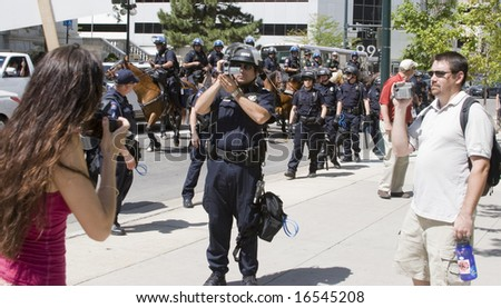 DENVER - AUGUST 25: A police officer records protesters who are documenting the area during the Democratic National Convention August 25, 2008 in Denver. - stock photo