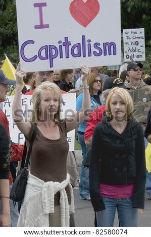 "DENVER, COLORADO – APRIL 15: Two women holding their ""I Love Capitalism"" sign at a Tea Party Patriots Tax Day Rally in Downtown Denver, April 15, 2011"
