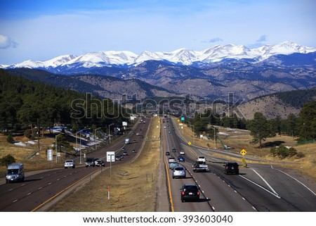 DENVER, COLORADO - February 27, 2016 - View of I-70 leading west into the snow capped Rocky Mountains - stock photo