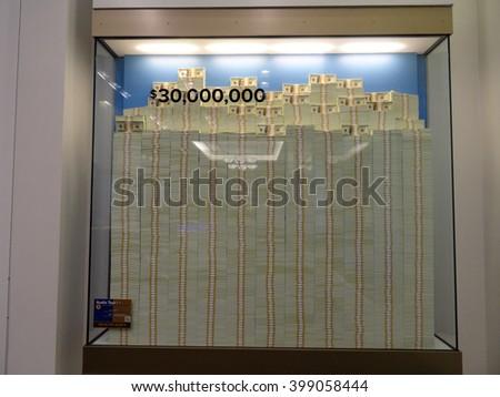 DENVER, COLORADO - JULY 7: Stack of Hundred dollar bills in glass display case equally 30 million dollars inside United States Mint in Denver, Colorado.  July 7, 2015. - stock photo