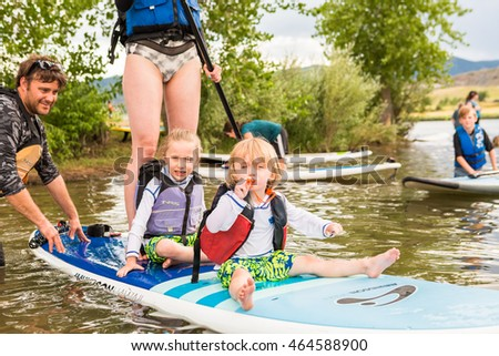 Denver, Colorado, USA-July 23, 2016. Family paddleboarding on small pond.