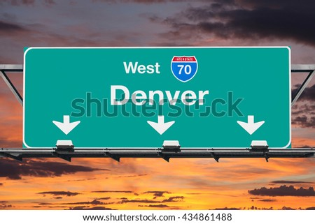 Denver Interstate 70 west highway sign with sunrise sky. - stock photo