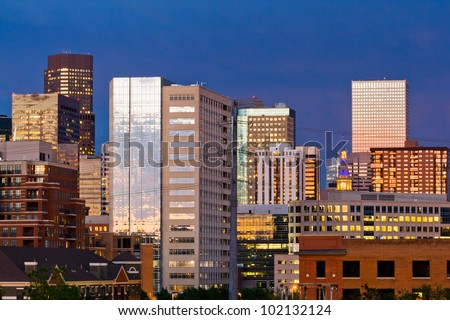 Denver skyline at dusk with colorful sunset reflection in the windows - stock photo