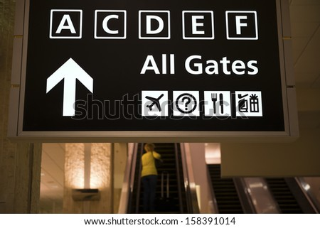 departure gates sign and escalators - stock photo