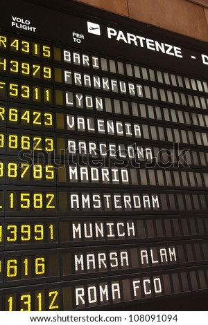 Departure schedule at an airport in Italy. Flights to Bari, Frankfurt, Lyon, Valencia, Barcelona, Madrid, Amsterdam, Munich, Marsa Alam and Rome. No airlines symbols visible. - stock photo