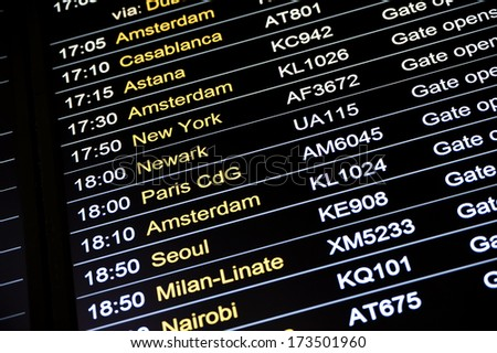 Departures display board at airport terminal showing international destinations flights to some of the world's most popular cities. Business or leisure travel concept - stock photo