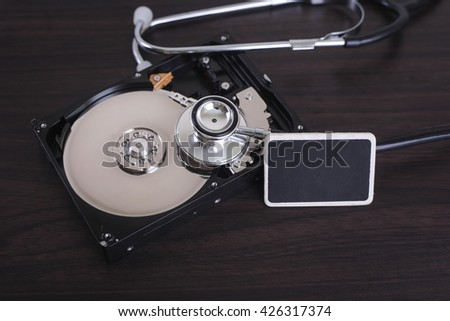Depiction of computer repairs and digital data recovery with a stethoscope scanning for lost information on a hard drive disc. - stock photo