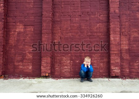 Depressed abused upset crying little child (boy, kid) sitting near big red brick wall - stock photo