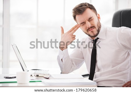Depressed and frustrated. Depressed young man in formalwear touching his temple with finger gun and keeping eyes closed while sitting at his working place - stock photo