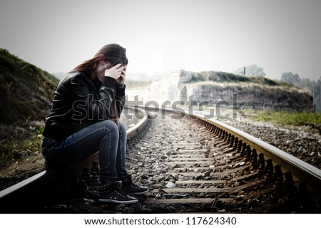 Depressed and lonely teenage girl with hands over her face sitting on the railroad - stock photo