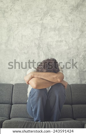Depressed and sad man on the couch in the room, covering face and crying in despair. Instagram Like Cross Processed Toned Image. - stock photo